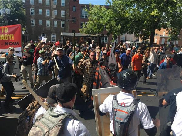 12日、米南部バージニア州シャーロッツビルで、白人至上主義のメンバーら(手前)と衝突する抗議グループ(上塚真由撮影)