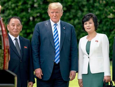 金聖恵氏(右)は、トランプ大統領(中)や、金英哲氏と記念写真に収まった=1日、ホワイトハウス(AP)