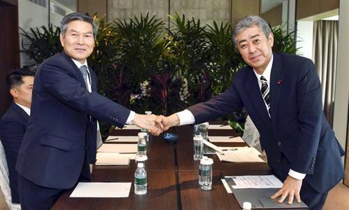 非公式会談で韓国の鄭景斗国防相(左)と笑顔で握手する岩屋毅防衛相=1日、シンガポール(韓国国防省提供・共同)
