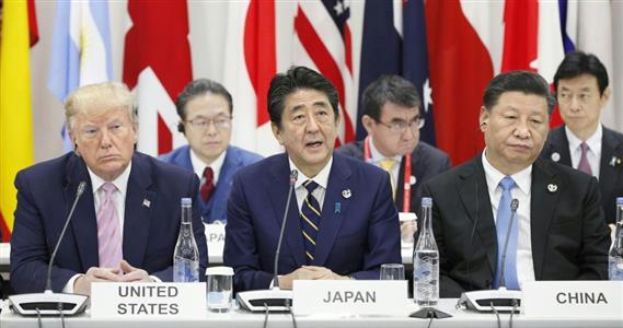 G20大阪サミットで行われたデジタル経済に関する首脳らの会合であいさつする安倍首相。左はトランプ米大統領、右は中国の習近平国家主席=28日午後、大阪市(共同)