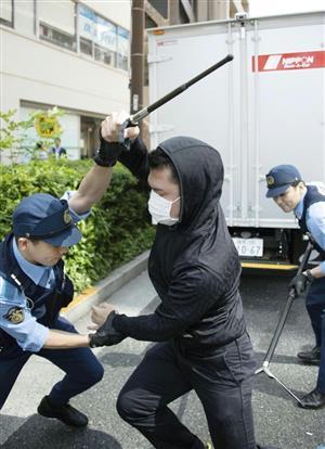 訓練で、レンタカーを借りた不審な男(中央)を取り押さえる警察官 =6月、東京都千代田区