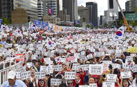韓国内では反文デモに多くの市民が参加した(共同)