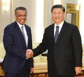 笑顔で握手するWHOのテドロス事務局長(左)と習主席=28日(AP)