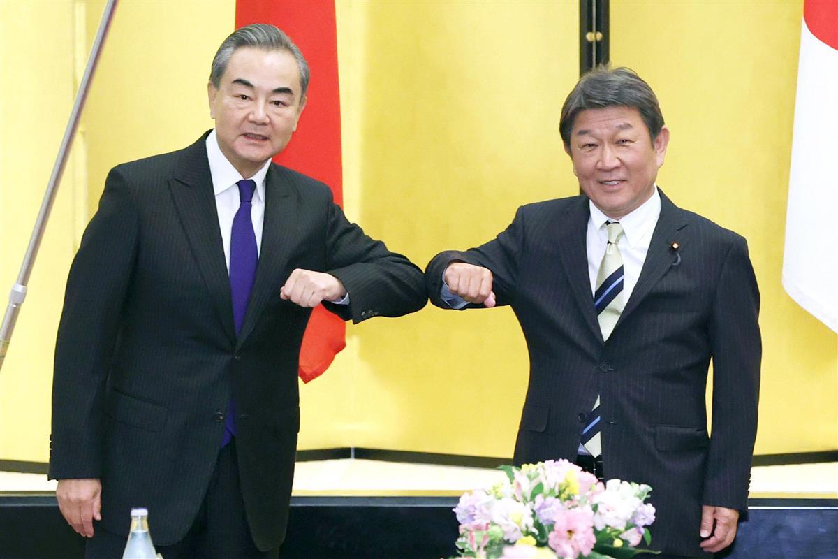 肘タッチを交わす王毅氏(左)と茂木外相=24日、東京都港区の飯倉公館(代表撮影)