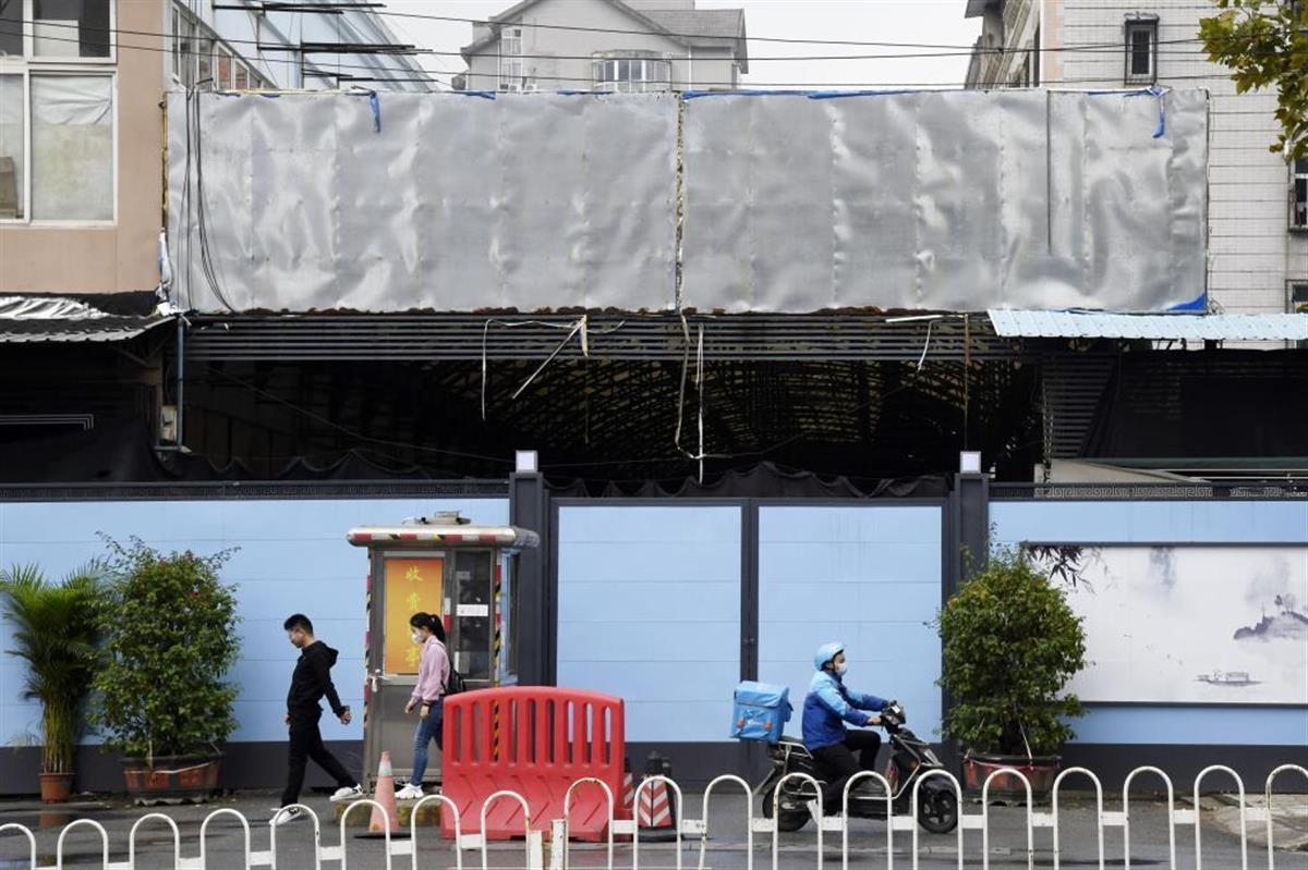看板の文字が消され、塀に囲まれた中国・武漢の華南海鮮卸売市場=10月(共同)