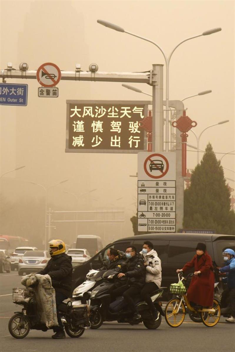 黄砂で黄色にかすむ北京市内で、外出を減らすよう注意を呼び掛ける電光表示=15日(共同)