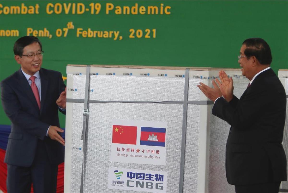 中国側から新型コロナワクチンを受け取るカンボジアの首相(右)=2月(AP)