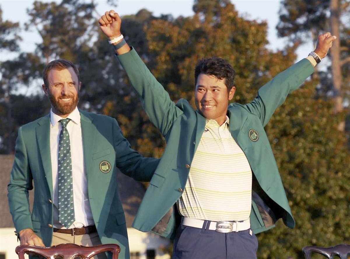優勝した松山は前年覇者のD・ジョンソンからグリーンジャケットを受け取った(ゲッティ=共同)