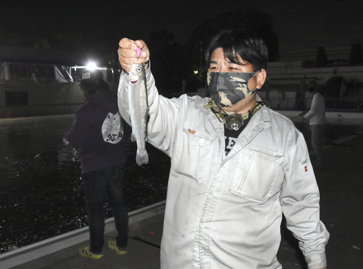「岸和田フィッシングパーク」のナイター営業で、ニジマスを釣り上げた男性=2日、大阪府岸和田市(共同)