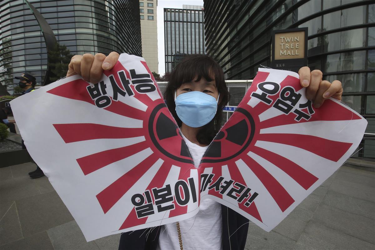 4月24日、ソウルの日本大使館前で行われた抗議デモで、旭日旗を模した旗を破る女性(AP)