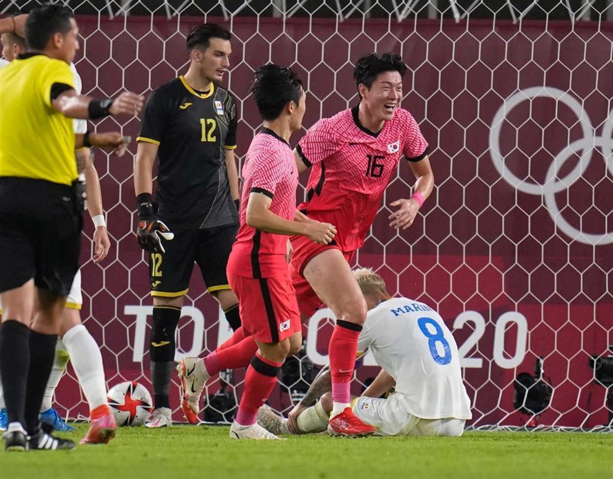 オウンゴールでうなだれるルーマニアのMFマリン(右奥)と喜ぶ韓国選手 =25日(AP)