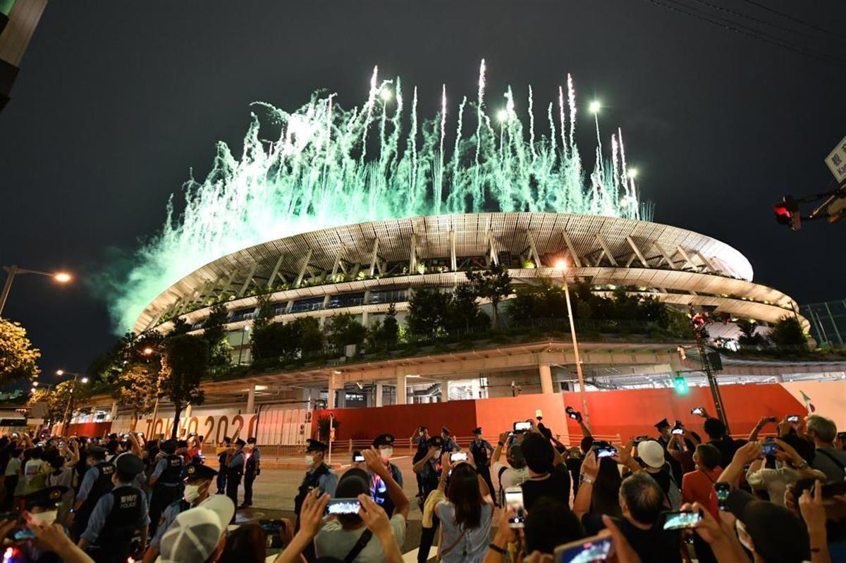 東京五輪開会式で国立競技場から打ち上がる花火を撮影する人々=23日午後8時4分、東京都渋谷区