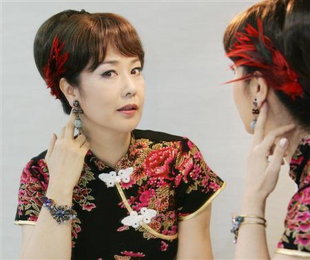 黒いチャイナ服を着て髪に赤い羽根飾りをつけた名取裕子